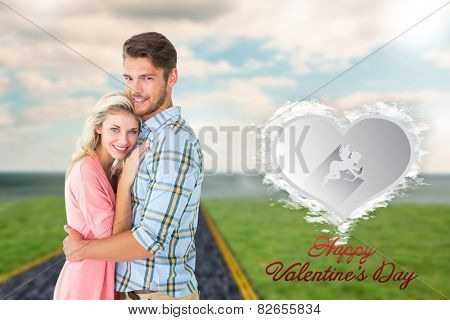 Attractive couple embracing and smiling at camera against cloud heart