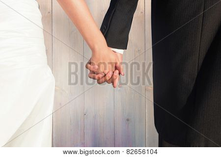 Close up of cute young newlyweds holding their hands against pale grey wooden planks