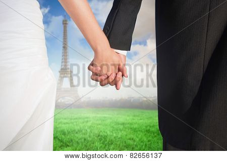 Close up of cute young newlyweds holding their hands against eiffel tower