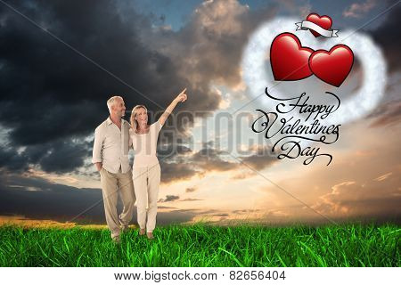 Smiling couple walking and pointing against green grass under blue and orange sky