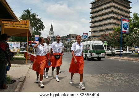 Four Black African Girl In Orange Skirts And White Blouses.