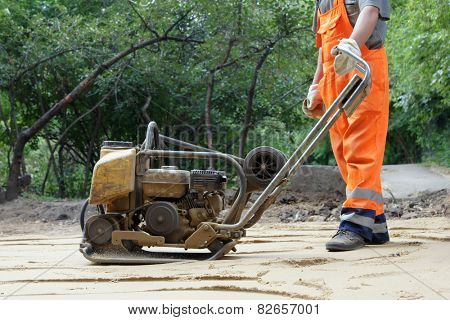 Worker in orange overalls with a plate compactor