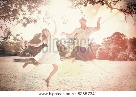 Cute couple jumping in the park together on a sunny day