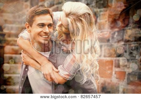 Man giving his pretty girlfriend a piggy back on a sunny day in the city