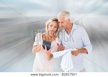 Anxious couple working out their bills against room with large window looking on city