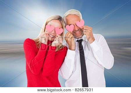 Silly couple holding hearts over their eyes against room with large window looking on city