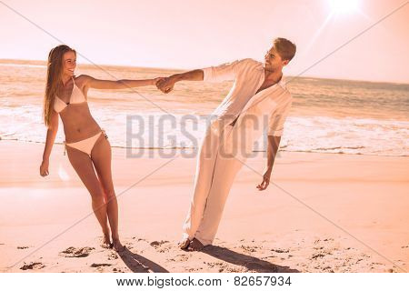 Couple holding hands and leaning to either side on the beach