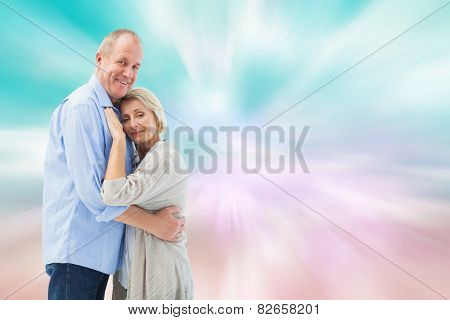 Happy mature couple hugging and smiling against digitally generated pink and blue girly design