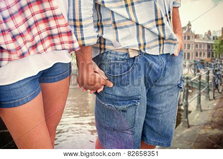 Couple in check shirts and denim holding hands against canal in amsterdam