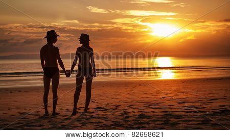 Pretty Couple Is Standing On The Tropical Sunset Background