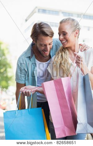 Attractive couple looking at shopping purchases on a sunny day in the city