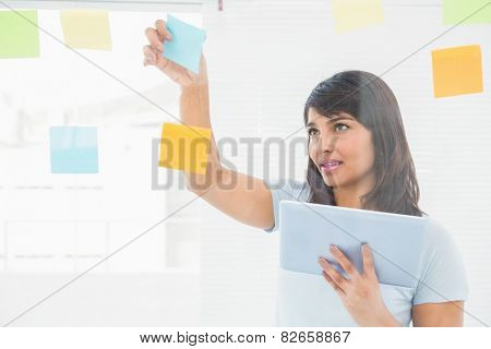 Businesswoman holding digital tablet and sticky notes in the office