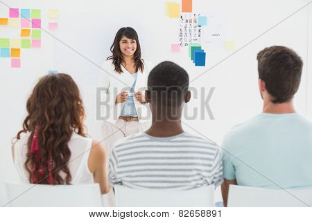 Smiling businesswoman presenting at group in the office