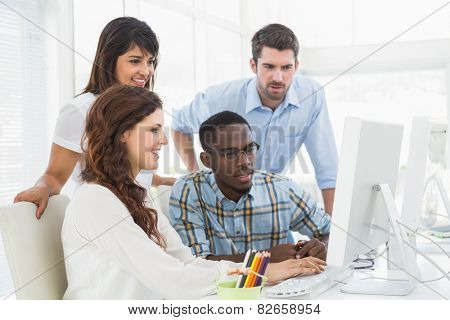 Concentrated coworkers using computer together in the office