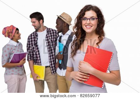 Smiling student standing with friends behind her on white background