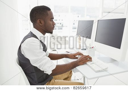 Classy businessman concentrating and using computer in the office
