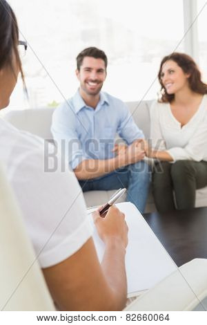 Smiling couple speaking with their therapist in the office