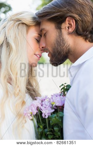 Attractive couple about to kiss each other on a sunny day in the city