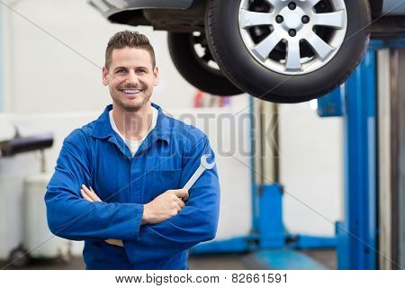 Mechanic smiling at the camera holding tool at the repair garage