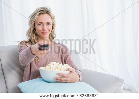 Smiling blonde changing tv channel while eating popcorn at home in the living room
