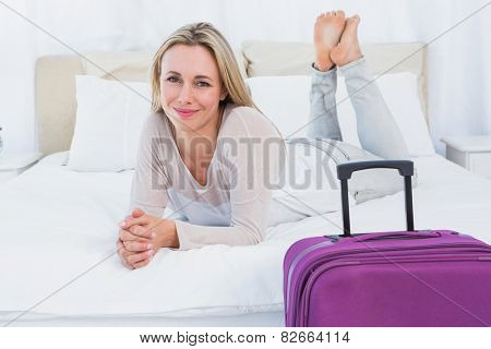 Smiling blonde lying on the bed near her baggage in hotel room