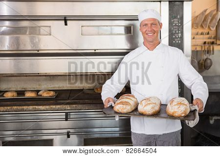 Happy baker holding tray of fresh bread in the kitchen of the bakery