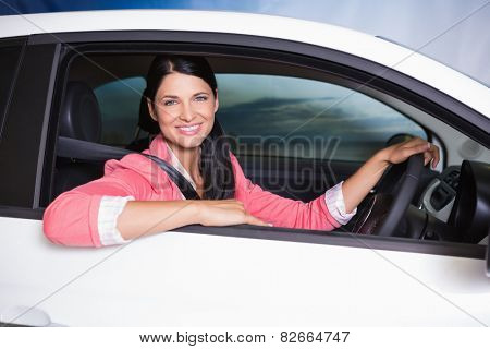 Smiling customer sitting at the wheel of a car for sale at new car showroom