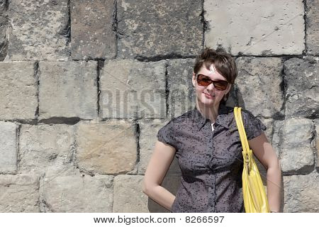Woman Poses On Ancient Wall Background