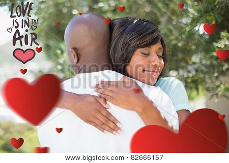 Happy couple hugging each other in garden against love is in the air
