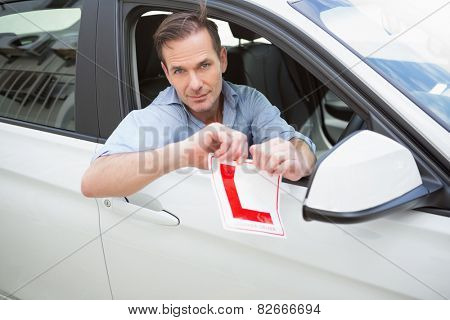 Smiling male driver tearing up his L sign in his car