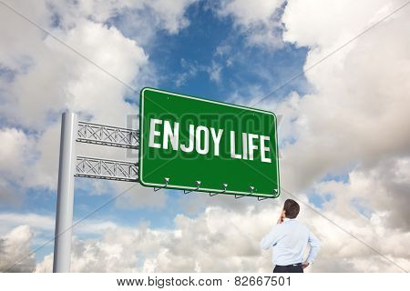 The word enjoy life and thinking businessman touching his chin against blue sky with white clouds