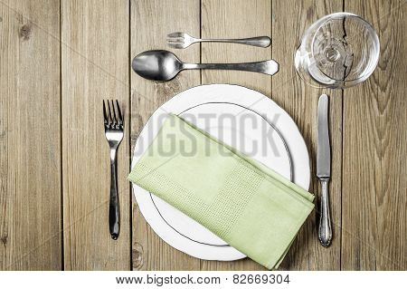Empty plates with a napkin dining room, cutlery set and empty wine glass on a wooden background