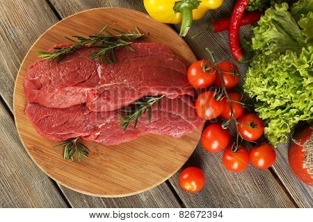 Raw beef steak on cutting board with vegetables and greens on wooden background