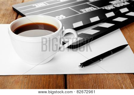 Movie clapper with paper, pen and cup of coffee on wooden planks background