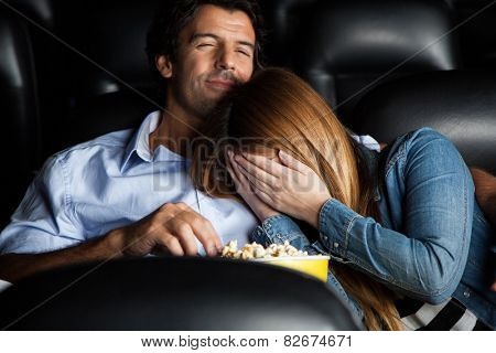 Frightened mid adult woman leaning on man while watching movie in cinema theater