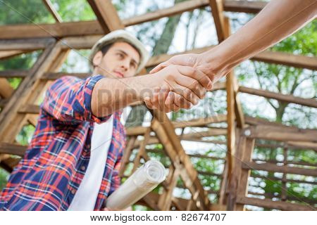 Low angle view of confident architect greeting colleague at construction site