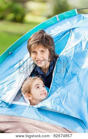 Portrait of happy siblings in tent at park