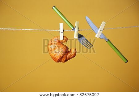 Fork, knife and croissant hanging from clothesline on color background
