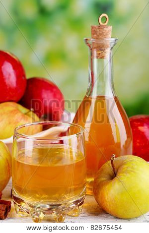 Apple cider in glass bottle with cinnamon sticks and fresh apples on cutting board, on bright background