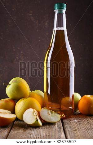bottle of apple vinegar with fresh apples on wooden table