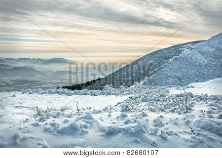 Beautiful mountains view at winter under sunset sky.