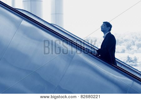 Asian Indian businessman going up escalator, side view in blue tone.