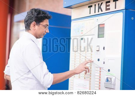 Asian Indian businessman buying transport ticket at vending machine.
