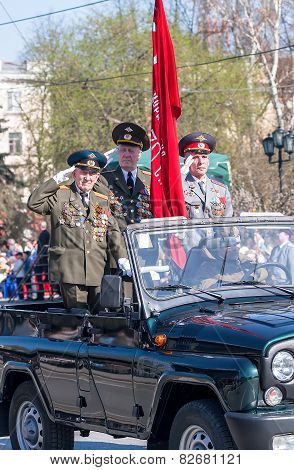 Veterans of World War 2 salute from SUV on parade