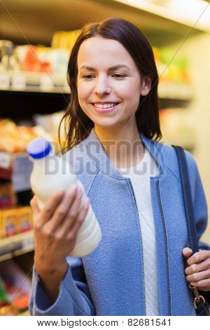 sale, shopping, consumerism and people concept - happy young woman holding milk bottle in market