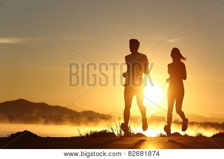 Silhouette Of A Couple Running At Sunset