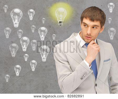 people, business, idea and doubts concept - young businessman thinking over gray background and light bulbs