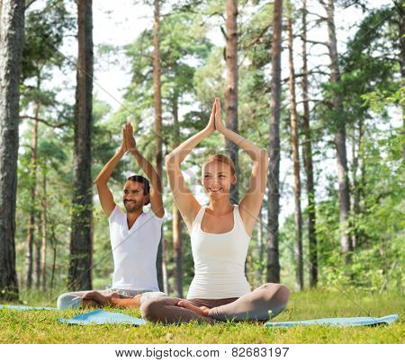 sport, fitness, yoga and people concept - smiling couple meditating and sitting on mats with raised hands over green woods background