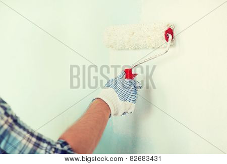 repair, building and home concept - close up of male in gloves painting wall with roller