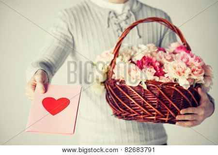 man with basket full of flowers and giving postcard.